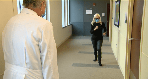 woman walking down hallway in doctors office
